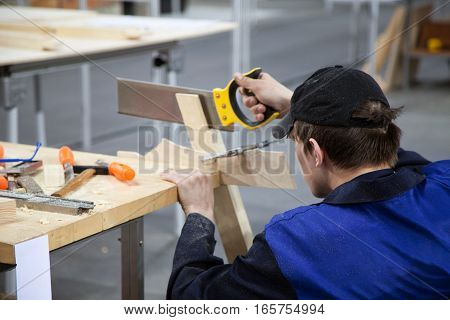 Khabarovsk Russia - April 24 2016:Carpenter in a blue uniform working with a saw and wood at the workshop. Young Caucasian man at the workbench with tools