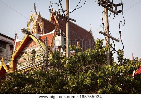 Beautiful Thai temple obscured by trees and electrical wires. Utility poles next to Buddhist shrine