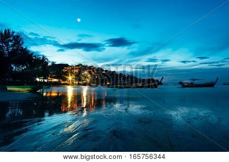 Romantic outdoor wide angle photography on a night beach of Phuket, Thailand. Sea shore with moon and light reflection and traditional thai boats floating in water of BangTao beach