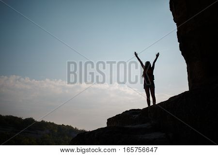 Girl with raised hands standing on hill against sun