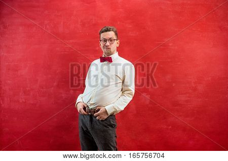 Young beautiful man on red studio background