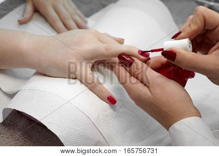 Manicurist nail paint red color to the girl client at beauty salon.