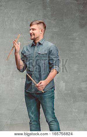 The young man holding two drumsticks over gray studio background