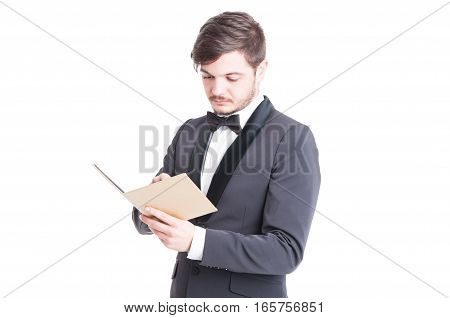 Handsome Man Wearing Tuxedo And Bowtie Looking At Notebook