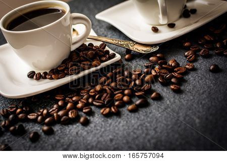 Two white cups of coffee with coffee bean on black stone background