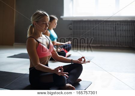 Two young women in yoga class making exercises. Girls do meditation pose for relaxation. Healthy lifestyle in fitness club, backlight, selective focus on blond, closeup