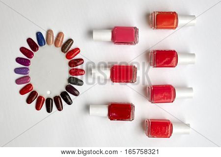 Red polish bottles and fake nails on a white background.