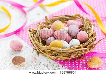 Easter chocolate candy eggs in straw nest - Easter treat for kids