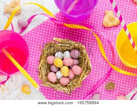 Easter chocolate candy eggs in nest on festive Easter table top view