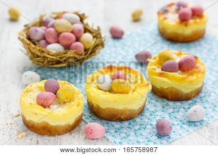 Easter nest cakes with colorful chocolate candy eggs on festive Easter table Easter holiday recipe