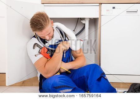 Exhausted Young Male Plumber Sleeping In Kitchen
