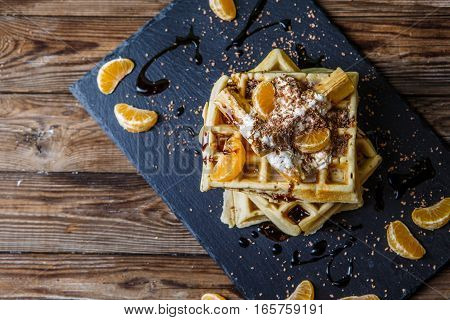Black board with homemade waffles, tangerines, chocolate