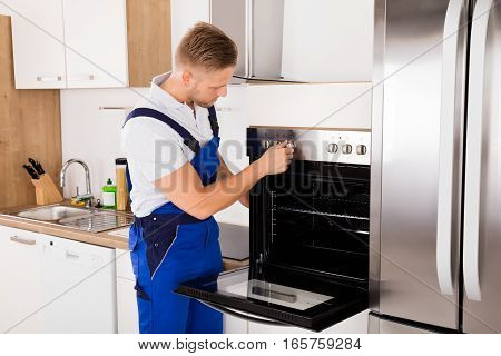 Young Male Technician In Overall Checking Oven In Kitchen