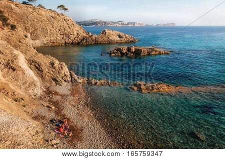 View of the cozy bay of Majorca with azure water hidden wild stone cliff beach and the tourists nudists of Paguera Mallorca Spain