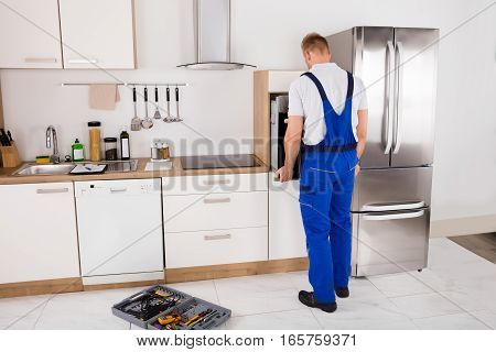 Young Male Technician In Overall Repairing Oven In Kitchen
