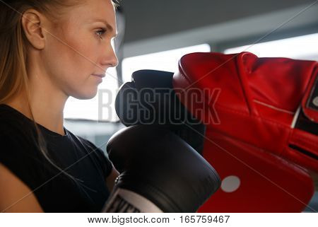 Beautiful young girl engaged in boxing in gym