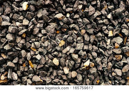 aggregate stone wall - rough gravel consisting of coarse dark gray stones and loose rocks at a stone pit.