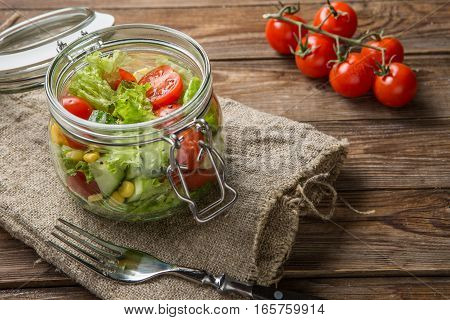 Vegetable salad on wooden table with napkin and fork