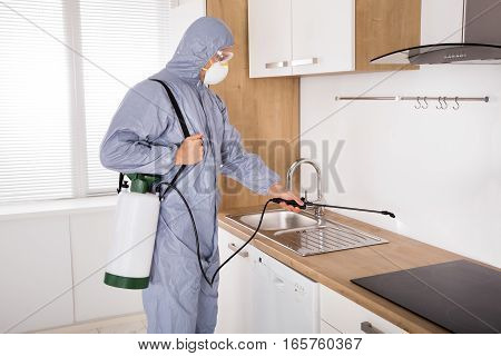 Pest Control Worker In Workwear Spraying Pesticide With Sprayer In Kitchen