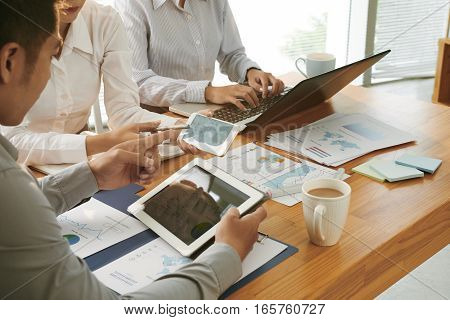 Business team using gadgets and financial reports in work