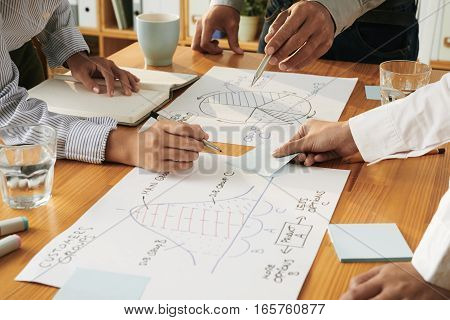 Hands of business people discussing charts and graphs