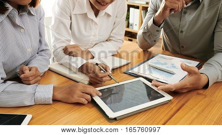 Cropped image of business team looking at graph on tablet computer