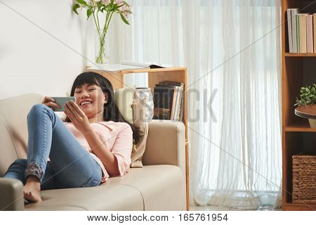 Young Vietnamese woman laughing when using application on smartphone