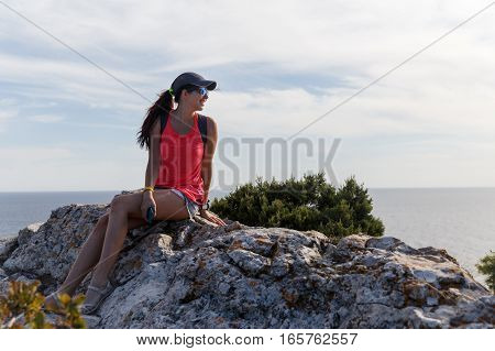 Young girl sits on hill on background of sea in afternoon