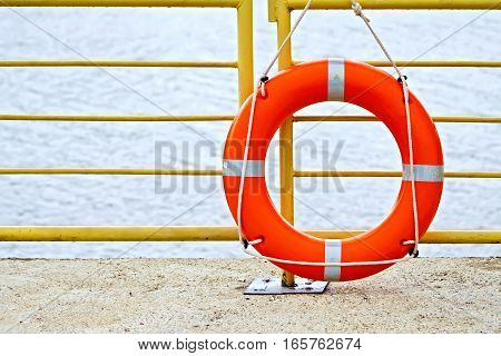 Lifebuoys red hanging on the yellow fence on the background of water