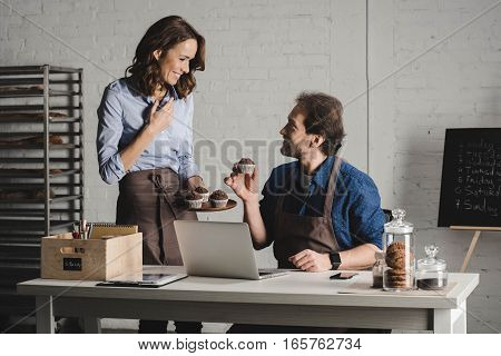Smiling male and female bakers talking and examining pastries in bakery