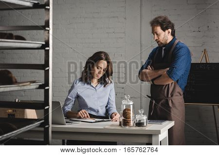 Male and female bakers discussing and making notes in bakery