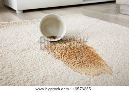 Close-up Of Coffee Spilling From Cup On Carpet