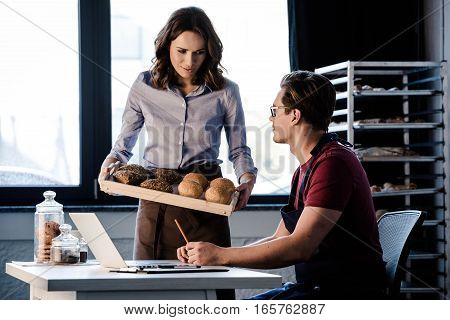 Male and female bakers interacting while examining pastries in bakery