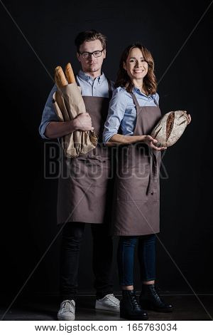 Male and female bakers holding different kinds of bread looking at the camera