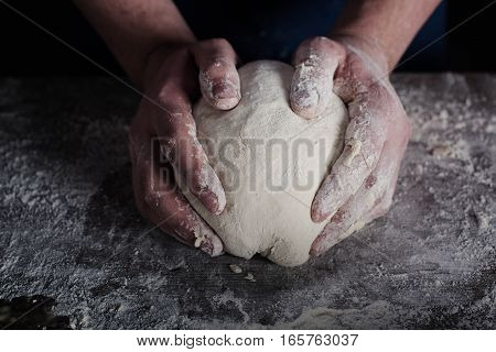 Man holding raw dough in hands ready to knead