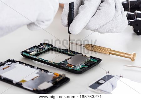 Close-up Of Person's Hand Wearing Glove Fixing Cellphone