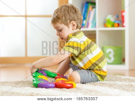 Little boy plays with a multi colored puzzle