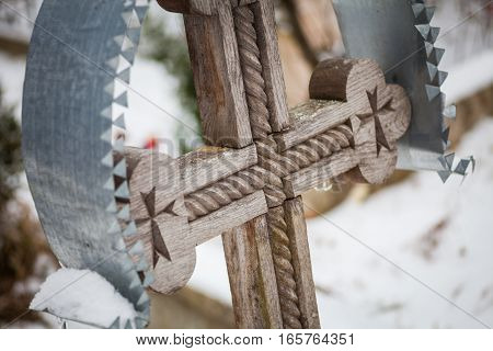 Close up shot of a wooden cross in a cemetery.