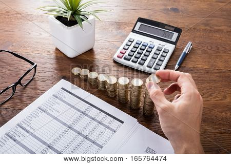 Person Stacking Coins With Calculator On Wooden Desk. Investment And Insurance Concept