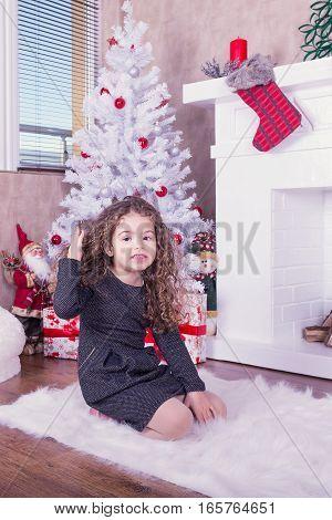 Portrait of pretty little girl near a fireplace in Christmas