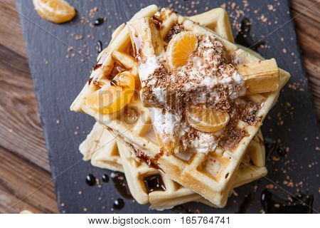 Black board with Belgian waffles with tangerines and chocolate. Food baackground.