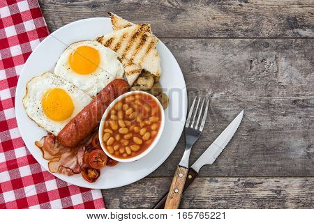 Traditional full English breakfast with fried eggs, sausages, beans, mushrooms, grilled tomatoes and bacon on wooden background.Top view