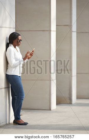 African-American woman standing at wall and using mobile app