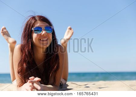 Girl in sunglasses on beach by sea