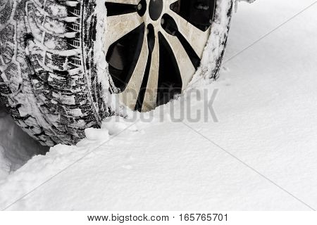 Car in the snow. Closeup of car tires in winter on the road covered with snow