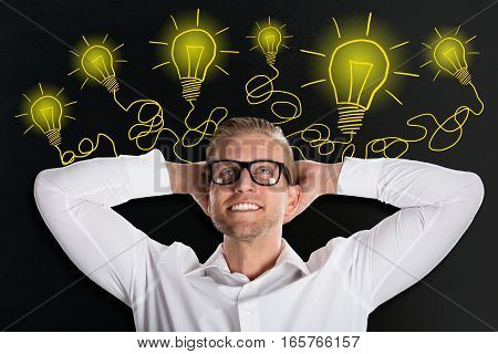 Handsome Smiling Young Man Looking Up With Creative Light Bulb Sketches On Blackboard