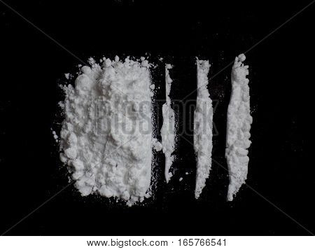Cocaine drug powder pile and lines on black background