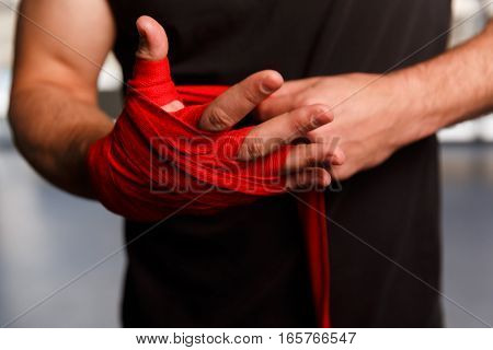 Athlete wears red boxing bandages on his hands
