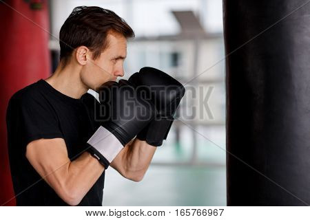 Portrait of young sportsman in boxing bag in hall