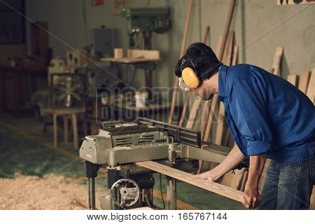 Carpenter cutting wooden board with electric planer